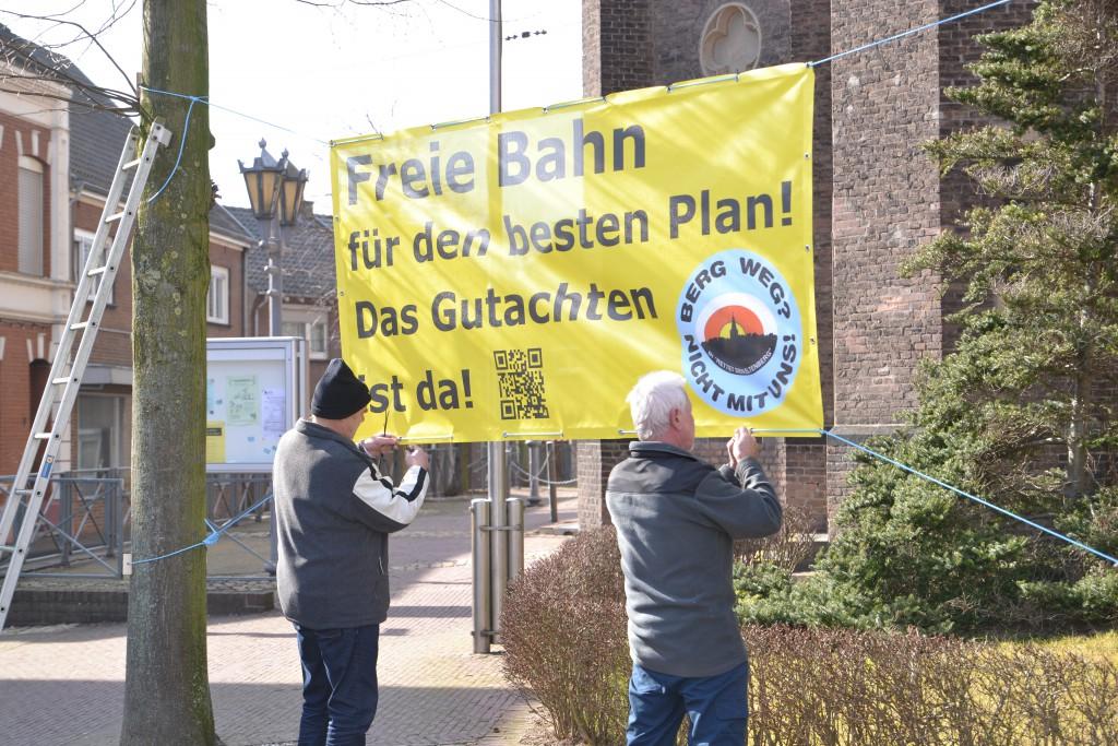 Winni Krüger und Hermann Weit hängen ein der Banner auf